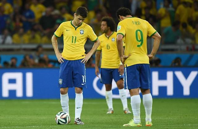 Brazil's midfielder Oscar (left) and Fred look dejected after Germany scored during the semi-final match at the Mineirao Stadium in Belo Horizonte during the 2014 FIFA World Cup on July 8, 2014 (AFP Photo/Patrik Stollarz)