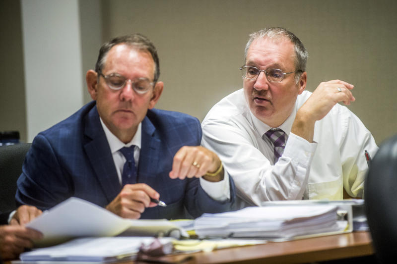 FILE - In this Aug. 22, 2018, file photo, Defendant Michael Prysby looks over paperwork with his defense attorneys at Genesee District Court in Flint, Mich. Prysby and Stephen Busch, two Michigan environmental regulators implicated in the Flint water scandal, have pleaded no contest to misdemeanors in exchange for more serious charges being dropped. (Jake May /The Flint Journal via AP, File)