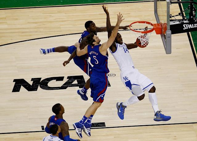 Michael Kidd-Gilchrist #14 of the Kentucky Wildcats is fouled as he goes to the basket against Elijah Johnson #15 and Jeff Withey #5 of the Kansas Jayhawks in the first half in the National Championship Game of the 2012 NCAA Division I Men's Basketball Tournament at the Mercedes-Benz Superdome on April 2, 2012 in New Orleans, Louisiana. (Photo by Chris Graythen/Getty Images)