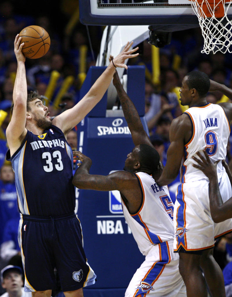 Memphis Grizzlies center Marc Gasol, left, of Spain, shoots in front of Oklahoma City Thunder center Kendrick Perkins, center, and forward Serge Ibaka, right, of the Republic of the Congo, in the third quarter of Game 1 of a second-round NBA basketball playoff series in Oklahoma City, Sunday, May 1, 2011. (AP Photo/Alonzo Adams)
