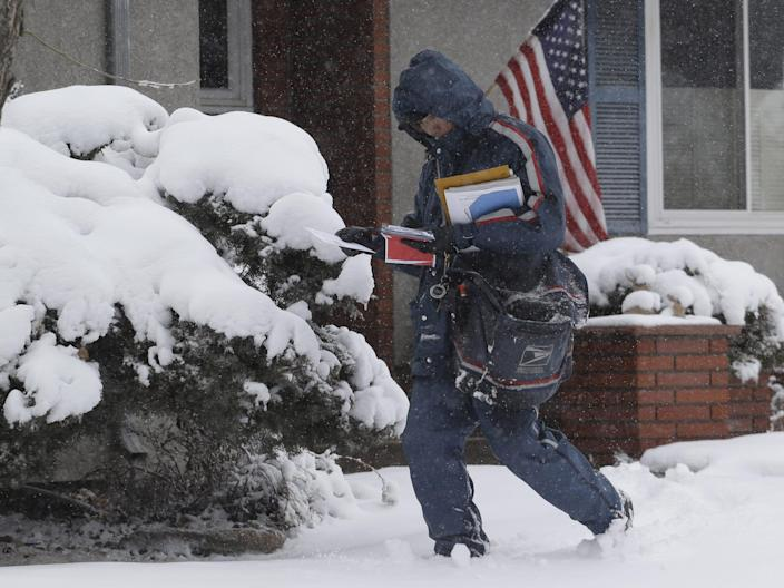 postal worker delivering snow in a snowstorm