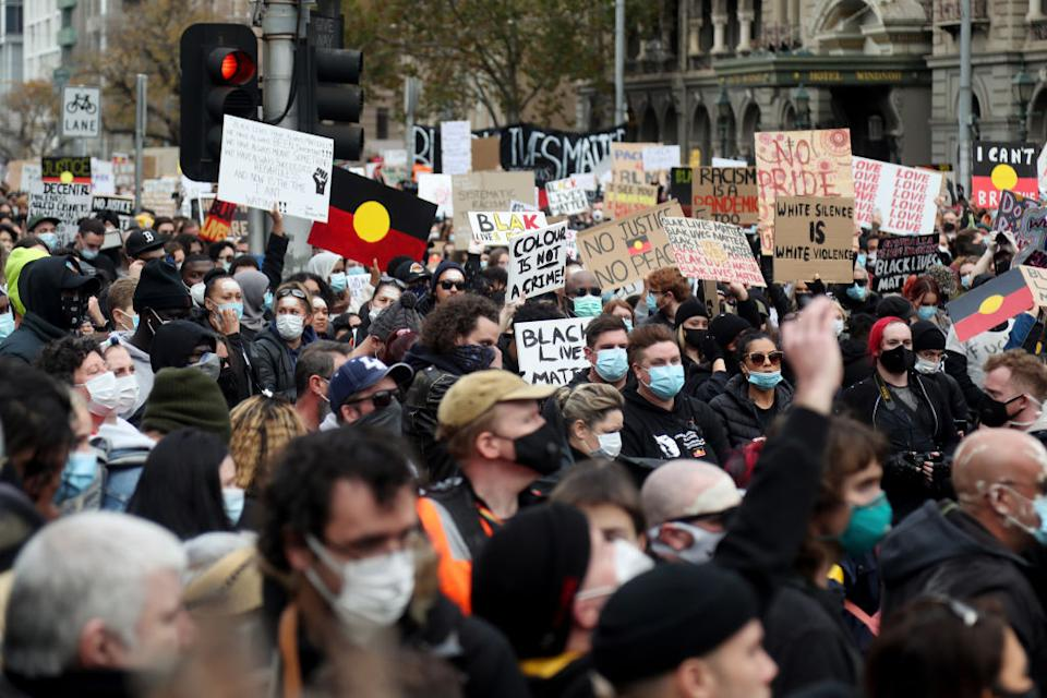 Protesters holding up signs on Bourke Street during the Black Lives Matter protest in Melbourne.