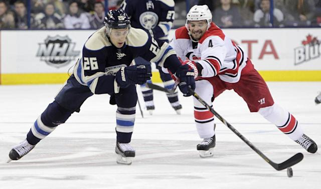 Columbus Blue Jackets' Corey Tropp, left, carries the puck upice as Carolina Hurricanes' Andrej Sekera, of Slovakia, defends during the second period of an NHL hockey game on Friday, Jan. 10, 2014, in Columbus, Ohio. (AP Photo/Jay LaPrete)