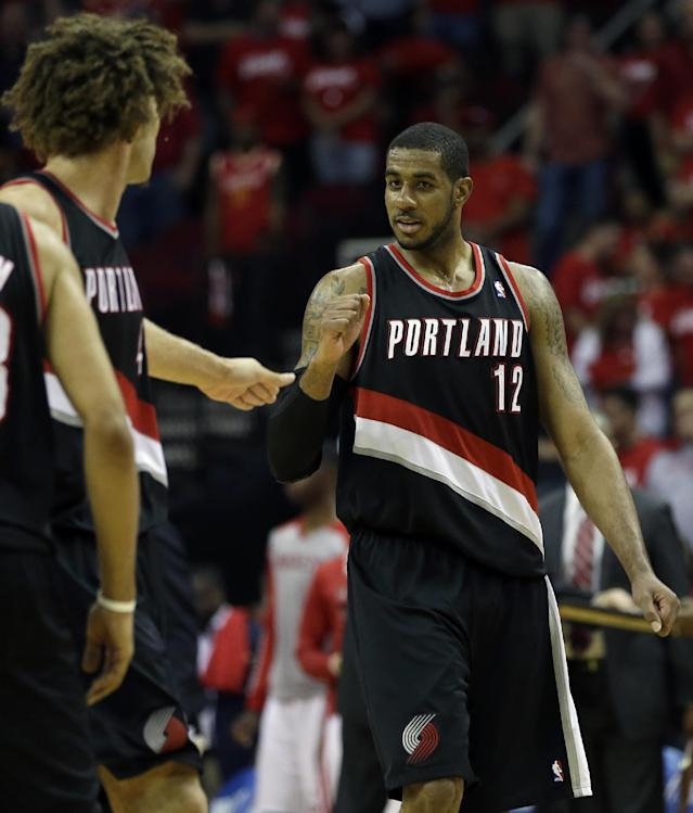 Portland Trail Blazers' LaMarcus Aldridge (12) celebrates with Robin Lopez, left, during the fourth quarter in Game 2 of an opening-round NBA basketball playoff series against the Houston Rockets Wednesday, April 23, 2014, in Houston. Portland won 112-105. (AP Photo/David J. Phillip)