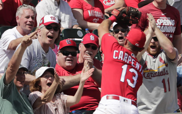 Fans react to St. Louis Cardinals third baseman Matt Carpenter (13) catching a fly ball headed for the stands in the fifth inning during an exhibition spring training baseball game against the Washington Nationals on Monday, March 11, 2019, in Jupiter, Fla. (AP Photo/Brynn Anderson)