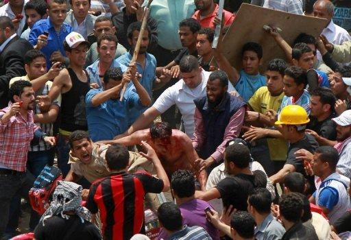 Egyptian protesters beat a man (C) who they accused of attacking them