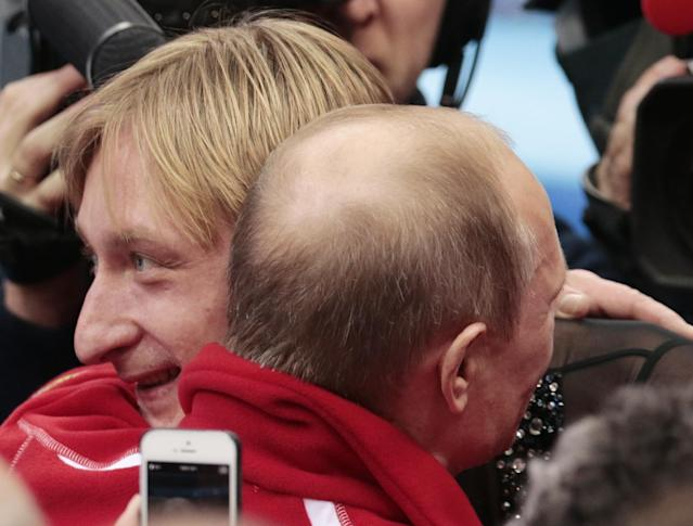 Russian President Vladimir Putin, right, embraces Evgeni Plushenko after Russia placed first in the team figure skating competition at the Iceberg Skating Palace during the 2014 Winter Olympics, Sunday, Feb. 9, 2014, in Sochi, Russia. (AP Photo/Ivan Sekretarev)