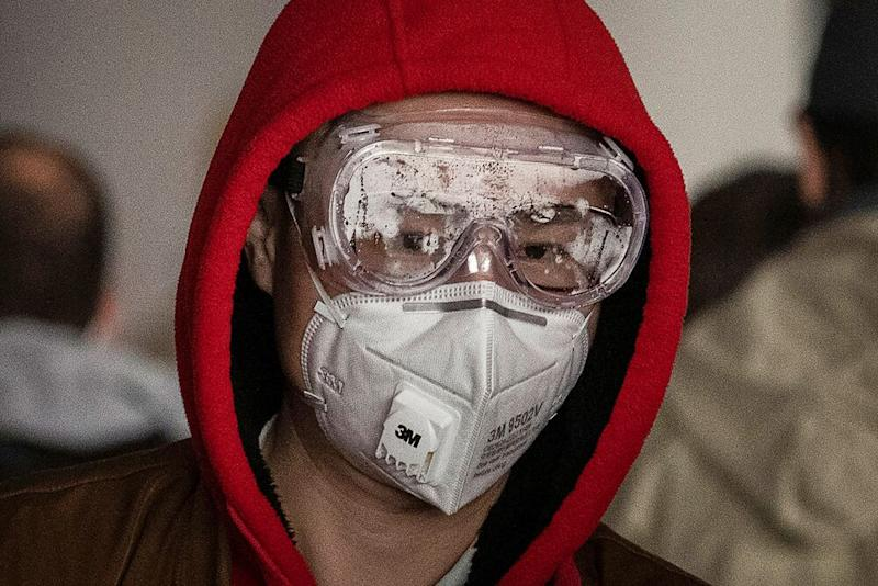 A man in Bejing wears a protective mask and goggles as he lines up to check in to a flight at Beijing Capital Airport on January 30, 2020, amid the outbreak of the coronavirus | Kevin Frayer/Getty