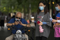 Women wearing face masks to help curb the spread of the coronavirus walk past a masked man browsing his smartphone on his bike in Beijing, Tuesday, July 20, 2021. (AP Photo/Andy Wong)