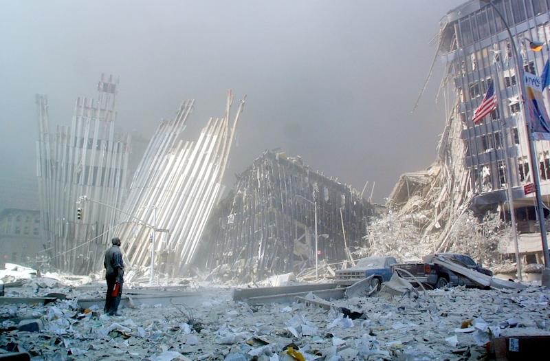 In this file photo taken on September 11, 2001, a man stands in the rubble, and calls out asking if anyone needs help, after the collapse of the first World Trade Center Tower in New York