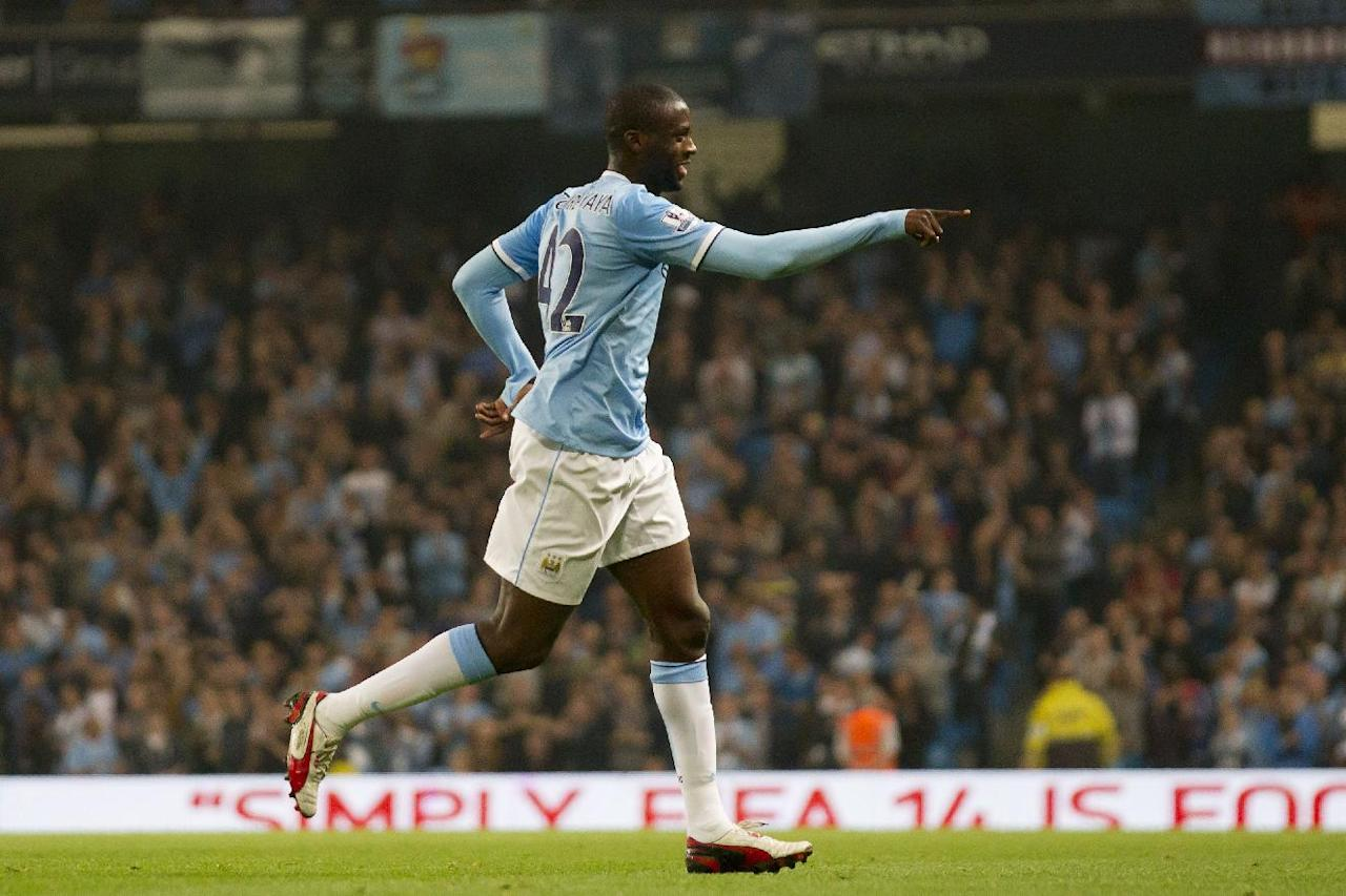 Manchester City's Yaya Toure celebrates after scoring against Wigan Athletic during their English League Cup soccer match at the Etihad Stadium, Manchester, England, Tuesday Sept. 24, 2013. (AP Photo/Jon Super)