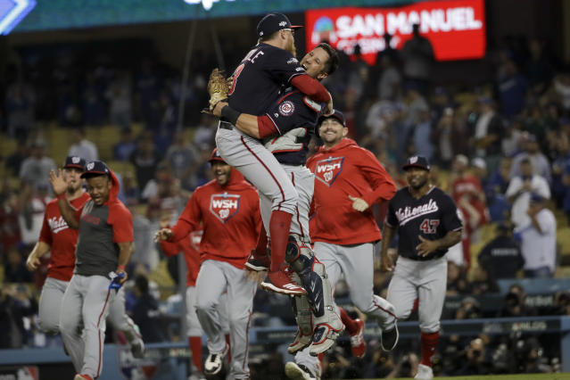 FILE - In this Oct. 9, 2019, file photo, Washington Nationals pitcher Sean Doolittle, center left, and catcher Yan Gomes leap in celebration after the team's 7-3 win in Game 5 of a baseball National League Division Series against the Los Angeles Dodgers in Los Angeles. At the suggestion of Washington's director of mental conditioning, Mark Campbell, Doolittle put lavender oil on the leather laces around the webbing of his glove for the postseason. It helped the lefty relax on the mound after a rocky regular season, much the way the bullpen as a whole went from disaster to asset in 2019, a trend the club hopes continues in 2020. (AP Photo/Marcio Jose Sanchez)