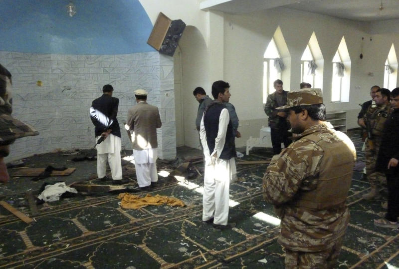 Afghan police and officials examine the mosque in Puli Alam, Logar Province, Afghanistan, where a bomb killed Gov. Arsallah Jamal, Tuesday, Oct. 15, 2013. No one immediately claimed responsibility for the attack but the Taliban have been targeting Afghan officials, military and NATO troops as part of a campaign to retake territory as international forces draw down ahead of a full pullout at the end of 2014. (AP Photo/Ahsanullah Majuze)