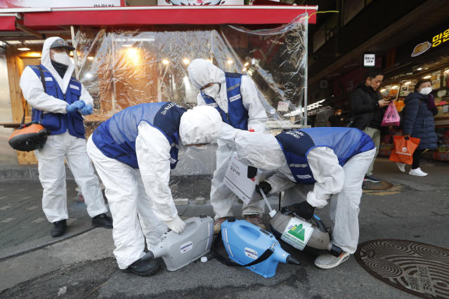 """Workers wearing protective gears prepare to spray disinfectant as a precaution against the coronavirus at a market in Seoul, South Korea, Monday, Feb. 24, 2020. South Korean President Moon Jae-in said his government had increased its anti-virus alert level by one notch to """"Red,"""" the highest level. It allows for the temporary closure of schools and reduced operation of public transportation and flights to and from South Korea. (AP Photo/Ahn Young-joon)"""