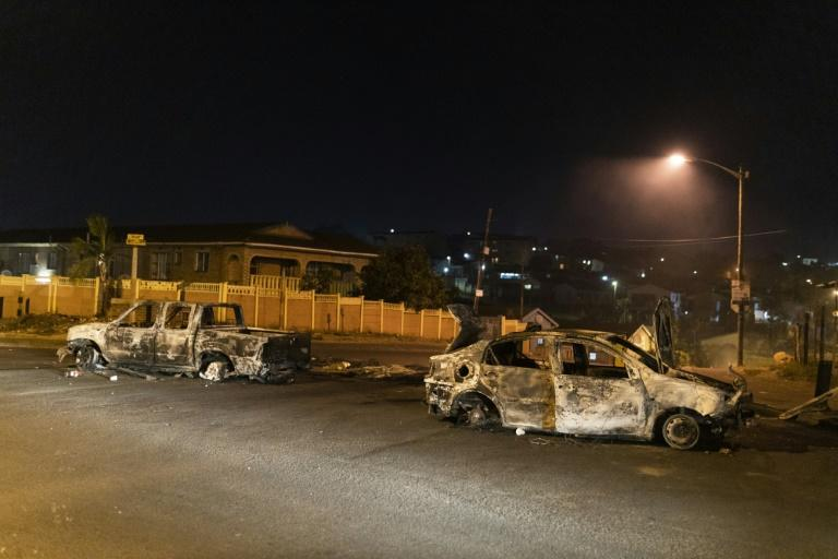 Violence: Burnt-out cars litter the township's streets