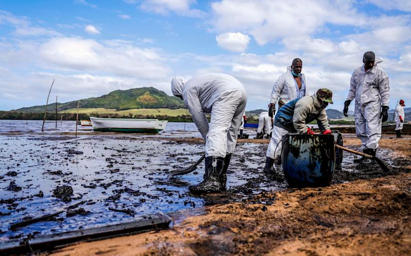 People scoop leaked oil from the vessel MV Wakashio, belonging to a Japanese company but Panamanian-flagged, that ran aground and caused oil leakage near Blue bay Marine Park in southeast Mauritius on August 9, 2020. -  - DAREN MAUREE /AFP