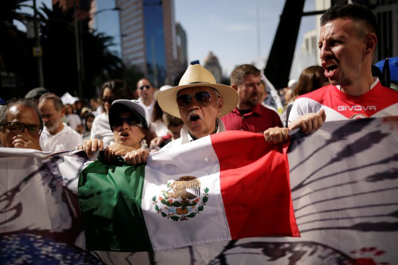 Demonstrators hold a Mexican flag during a march to protest against violence on the first anniversary of President Andres Manuel Lopez Obrador taking office, in Mexico City