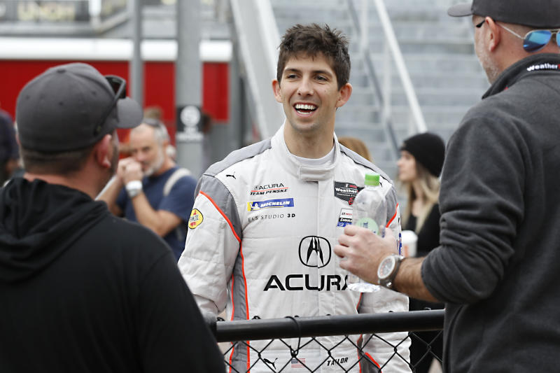 """FILE - In this Jan. 23, 2020, file photo, driver Ricky Taylor, center, from ACURA Team Penske, talks to fans in the garage before qualifying for the Rolex 24 hour auto race at the Daytona International Speedway, in Daytona Beach Fla. t the Team Penske annual preseason breakfast, Roger Penske took the unusual step to single out one specific aspect of his massive organization. """"He doesn't normally point out an event, maybe the Indy 500 or the Daytona 500, but this year he said 'We have to be better at the Rolex 24,'"""" said Ricky Taylor, full-time driver of the No. 7 Acura Team Penske. (AP Photo/Reinhold Matay, File)"""