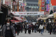 "People wearing face masks walk through a market in Seoul, South Korea, Thursday, March 4, 2021. South Korea's central bank says the country's economy shrank for the first time in 22 years in 2020 as the coronavirus pandemic destroyed service industry jobs and depressed consumer spending. The banner reads: ""Lets' overcome Corona 19 together."" (AP Photo/Ahn Young-joon)"
