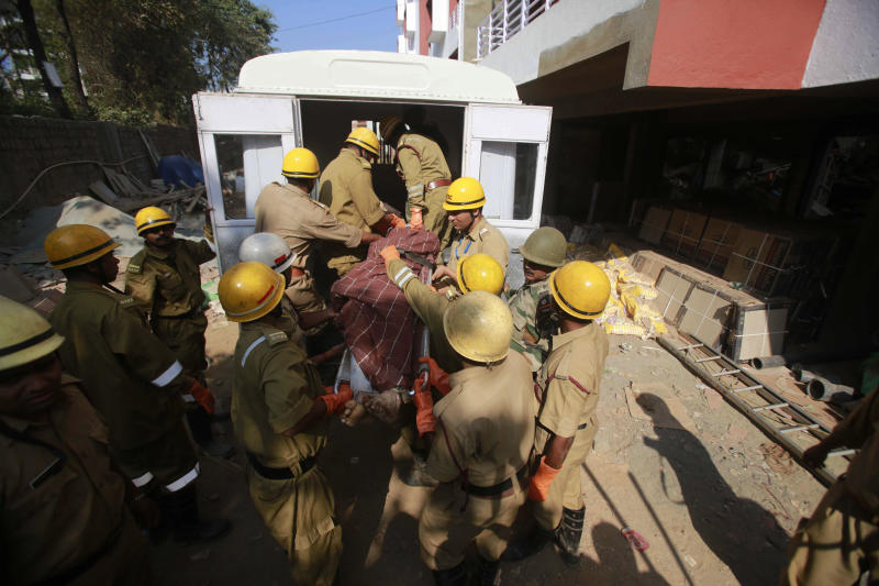 Rescue workers carry the body of a victim amid the debris of a building that collapsed in Canacona, about 70 kilometers (44 miles) from Goa state capital Panaji, India, Sunday, Jan. 5, 2014. A five-story building under construction in the southern Indian state of Goa collapsed on Saturday, killing at least a dozen people and leaving dozens more feared trapped under the rubble, police said. (AP Photo/Rafiq Maqbool)