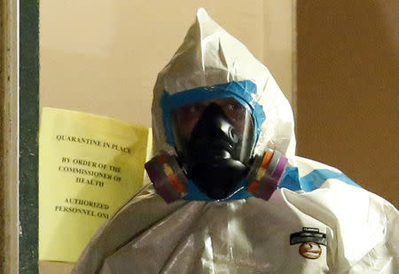 A worker in a hazardous material suit steps out of an apartment unit where a man diagnosed with the Ebola virus was staying in Dallas, Texas, October 5, 2014.  REUTERS/Jim Young