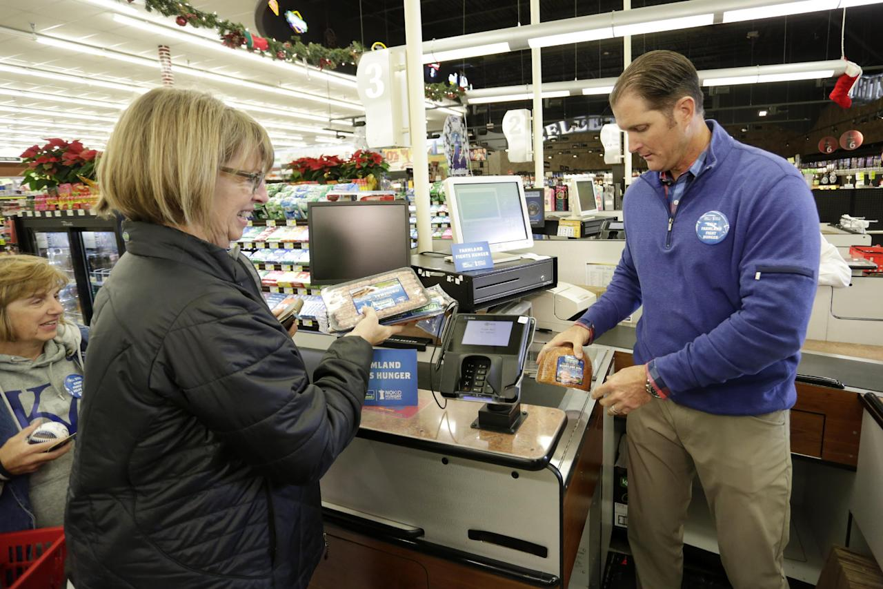 IMAGE DISTRIBUTED FOR FARMLAND - Kansas City Royals legend Mike Sweeney, right, checks out a customer at a local Price Chopper during the Farmland Fights Hunger event, Wednesday, Nov. 30, 2016, in Kansas City, Mo. For every Farmland product purchased through December 31st, twenty five cents will be donated to No Kid Hungry. (Colin E. Braley/AP Images for Farmland)