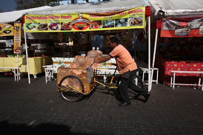 In this Jan. 4, 2014 photo, a vendor pushes his bicycle cart filled with 18-liter jugs of bottled water to sell to owners of street food stalls in Mexico City. Bad tap water accounts in part for Mexico being the highest consumer of bottled water and sweetened drinks. A law recently approved by Mexico City's legislators will require all restaurants to install filters, offering patrons free, apparently drinkable potable water that won't lead to stomach problems and other ailments. With an obesity epidemic looming nationwide, the city's health department decided to back the water initiative. (AP Photo/Marco Ugarte)
