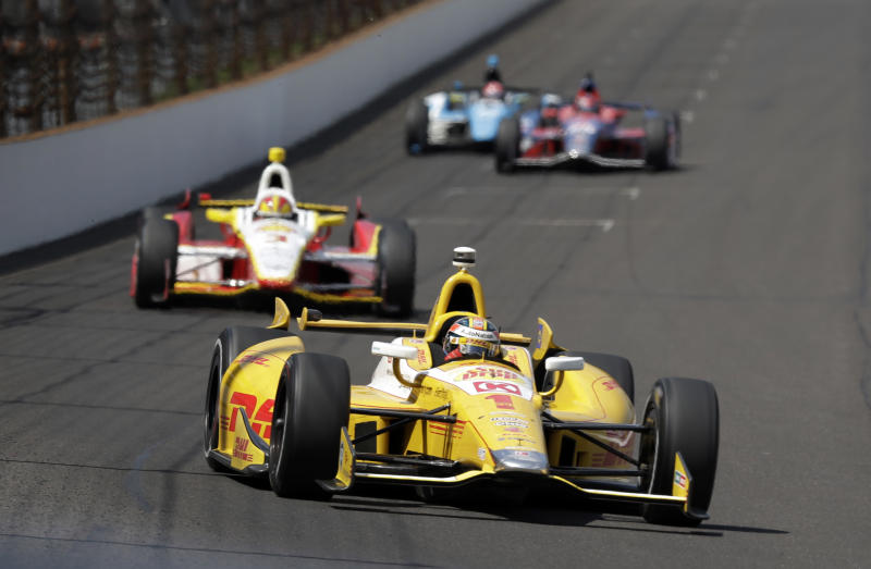 Ryan Hunter-Reay leads Helio Castroneves, of Brazil, into the first turn during a practice session on the second day of qualifications for the Indianapolis 500 auto race at the Indianapolis Motor Speedway in Indianapolis, Sunday, May 19, 2013. (AP Photo/Darron Cummings)