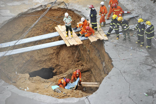 ATTENTION EDITORS - VISUAL COVERAGE OF SCENES OF INJURY OR DEATH Rescue workers carry out the body of a victim in a road cave-in accident in this picture taken through a security window in Shenzhen, Guangdong province May 21, 2013. REUTERS/China Daily (CHINA - Tags: DISASTER ENVIRONMENT TPX IMAGES OF THE DAY) CHINA OUT. NO COMMERCIAL OR EDITORIAL SALES IN CHINA. TEMPLATE OUT - RTXZUTI