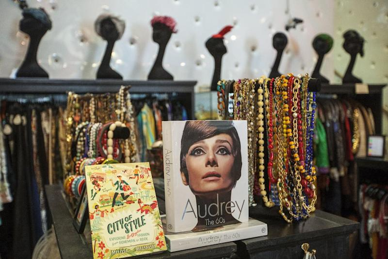 """In this photo taken Thursday, Feb. 21, 2013, a 1960's fashion book of actress Audrey Hepburn is displayed with vintage jewelry at """"The Way We Wore,"""" a Hollywood high-end vintage store owned by Doris Raymond in the La Brea District of Los Angeles. Raymond's vintage clothing and accessories store is featured in the reality TV series, """"L.A. Frock Stars,"""" which debuts March 7, 2013 on the Smithsonian Channel. (AP Photo/Damian Dovarganes)"""