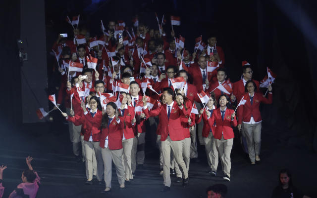 Singapore athletes hold flags during the opening ceremony of the 30th South East Asian Games at the Philippine Arena, Bulacan province, northern Philippines on Saturday, Nov. 30, 2019. (AP Photo/Aaron Favila)