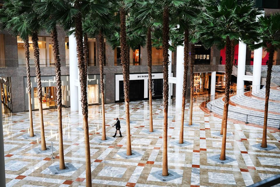"A man walks through a deserted Brookfield Place mall in lower Manhattan on March 29. According to the Brookfield Place <a href=""https://bfplny.com/covid-19-updates/"" rel=""nofollow noopener"" target=""_blank"" data-ylk=""slk:website"" class=""link rapid-noclick-resp"">website</a>, ""[All] common areas of the complex are temporarily closed except to serve as thoroughfares to and from offices for essential operations."""