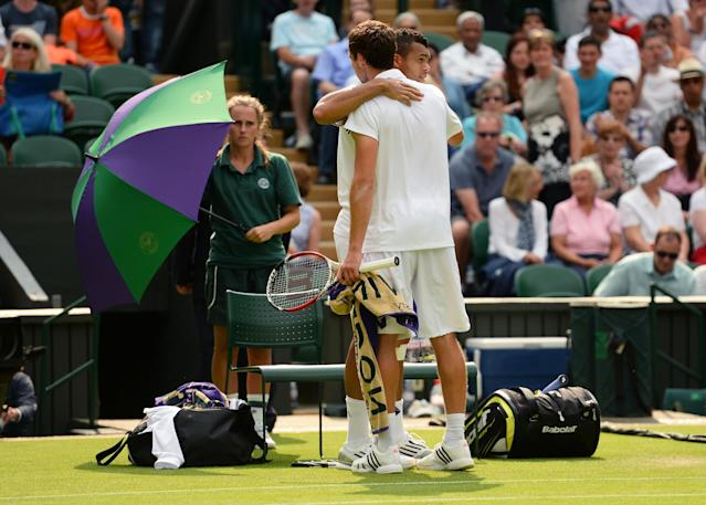 LONDON, ENGLAND - JUNE 26: Jo-Wilfried Tsonga of France is consoled by Ernests Gulbis of Latvia after retiring from their Gentlemen's Singles second round match on day three of the Wimbledon Lawn Tennis Championships at the All England Lawn Tennis and Croquet Club on June 26, 2013 in London, England. (Photo by Mike Hewitt/Getty Images)