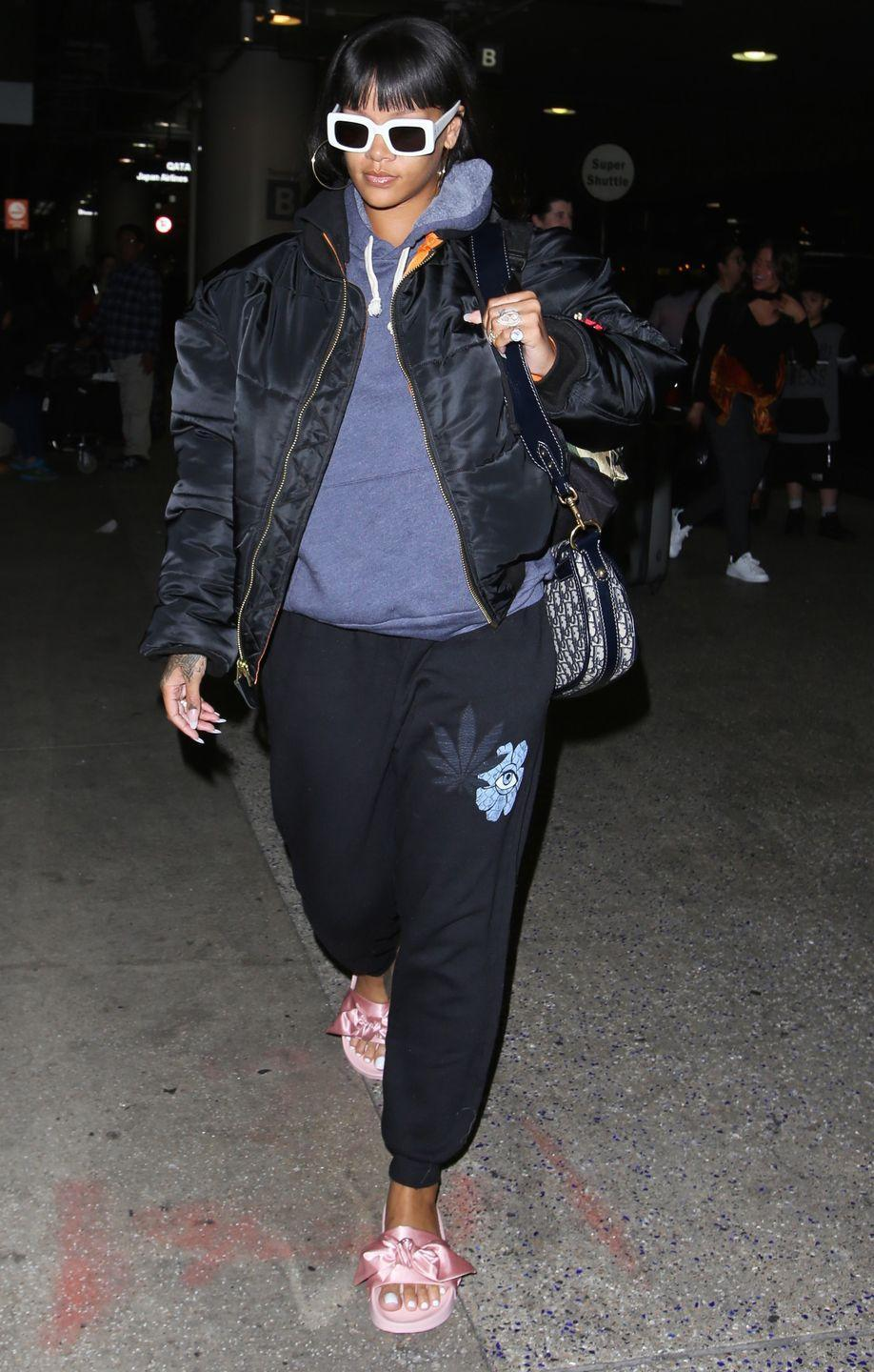 <p>In a JAxSweetleaf sweatshirt, black bomber, marijuana leaf-embellished sweatpants, Fenty x Puma by Rihanna slides, a Dior bag and white RAEN sunglasses.</p>