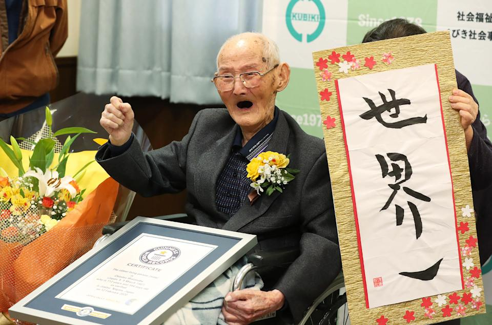 """In this handout picture taken and released by Guineess World Records LTD. via Jiji Press on February 12, 2020 Japanese Chitetsu Watanabe, aged 112, poses next to the calligraphy reading in Japanese 'World Number One' after he was awarded as the world's oldest living male in Joetsu, Niigata prefecture. - A 112-year-old Japanese man who believes smiling is the key to longevity has been recognised as the world's oldest male, Guinness World Records said on February 12, 2020. (Photo by STR / 2019 Guinness World Records Ltd via Jiji Press / AFP) / Japan OUT / RESTRICTED TO EDITORIAL USE - MANDATORY CREDIT """"AFP PHOTO /  2019 GUINNESS WORLD RECORDS LTD. / JIJI PRESS"""" - NO MARKETING - NO ADVERTISING CAMPAIGNS - DISTRIBUTED AS A SERVICE TO CLIENTS (Photo by STR/2019 Guinness World Records Ltd /AFP via Getty Images)"""