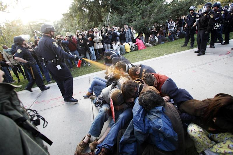 In this Friday, Nov. 18, 2011, photo University of California, Davis Police Lt. John Pike uses pepper spray to move Occupy UC Davis protesters while blocking their exit from the school's quad Friday in Davis, Calif. Two University of California, Davis police officers involved in pepper spraying seated protesters were placed on administrative leave Sunday, Nov. 20, 2011,  as the chancellor of the school accelerates the investigation into the incident. (AP Photo/The Enterprise, Wayne Tilcock)