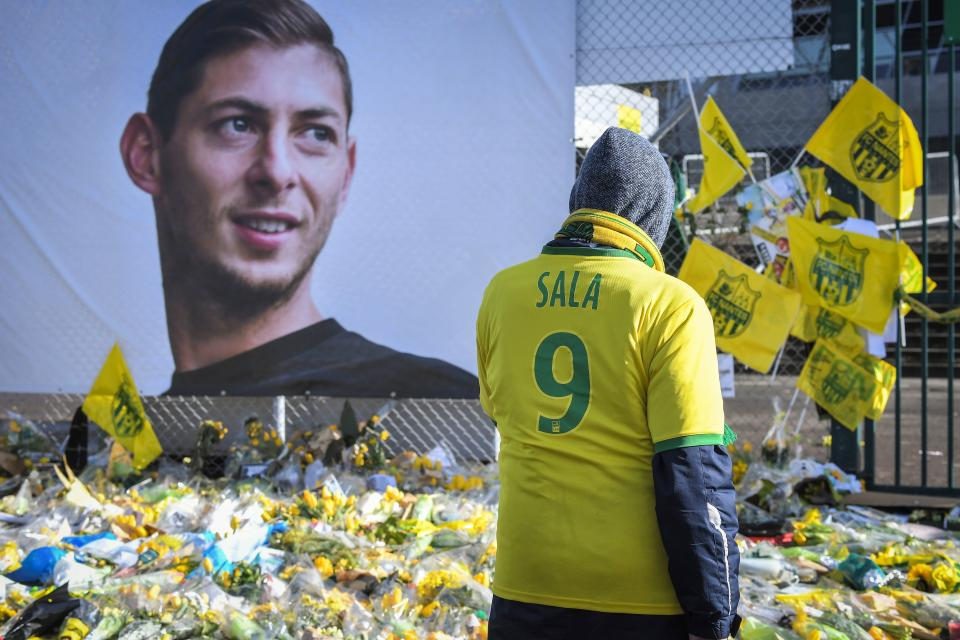 Supporters pay tribute and look at yellow flowers displayed in front of the portrait of Argentinian forward Emiliano Sala at the Beaujoire stadium in Nantes, on February 10, 2019. - FC Nantes football club announced on February 8, 2019 that it will freeze the #9 jersey as a tribute to Cardiff City and former Nantes footballer Emiliano Sala who died in a plane crash in the English Channel on January 21, 2019. (Photo by LOIC VENANCE / AFP)        (Photo credit should read LOIC VENANCE/AFP/Getty Images)