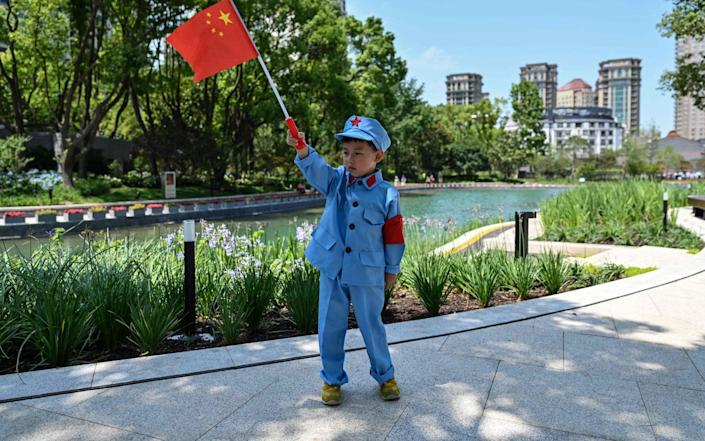 A child holds a Chinese flag near the museum of the First National Congress of the Chinese Communist Party - HECTOR RETAMAL/AFP via Getty Images