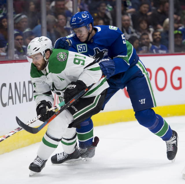 Dallas Stars center Tyler Seguin (91) and Vancouver Canucks defenseman Tyler Myers (57) work for the puck during the second period of an NHL hockey game Thursday, Nov. 14, 2019, in Vancouver, British Columbia. (Jonathan Hayward/the Canadian Press via AP)