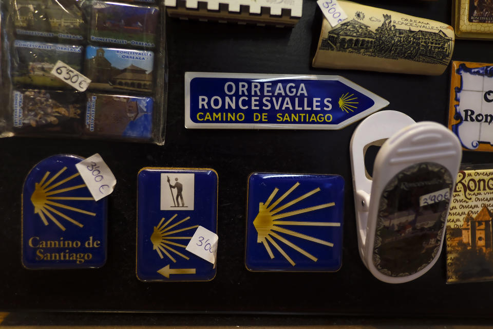 Souvenirs of St. James Way are displayed for sale at a shop in Roncesvalles, where the French route of Spain Saint James Way starts, Northern Spain, Saturday, April 10, 2021. The pilgrims are trickling back to Spain's St. James Way after a year of being kept off the trail due to the pandemic. Many have committed to putting their lives on hold for days or weeks to walk to the medieval cathedral in Santiago de Compostela in hopes of healing wounds caused by the coronavirus. (AP Photo/Alvaro Barrientos)