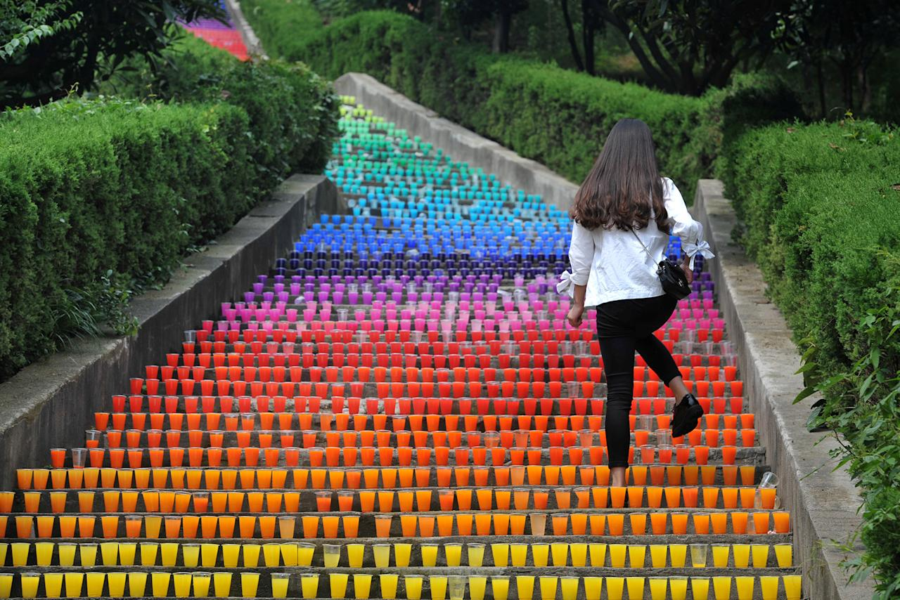 <p>A woman walks on steps lined with plastic cups, an art project of four college students, in Wuhan, Hubei Province, China, May 24, 2016. (Stringer/REUTERS) </p>