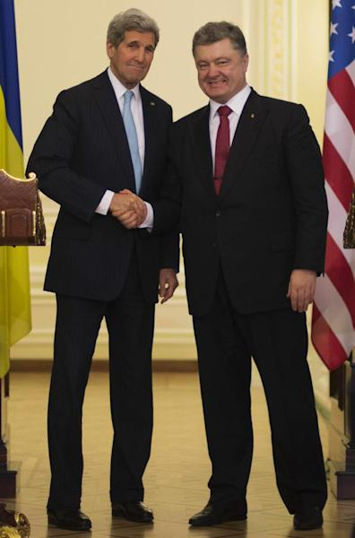Ukrainian President Petro Poreshenko (R) shakes hands with US Secretary of State John Kerry (L) after delivering a statement following a bilateral meeting in Kiev, on February 5, 2015 (AFP Photo/Jim Watson)