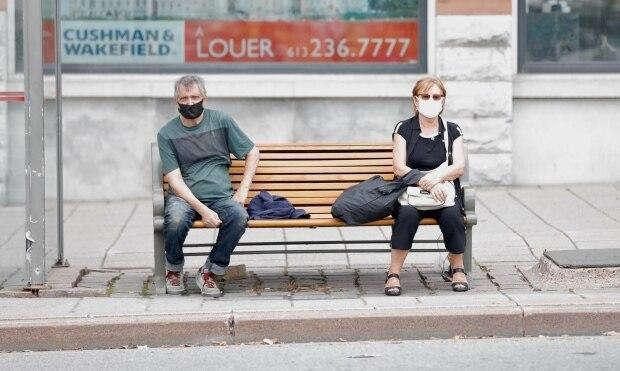 People in masks wait for a bus on opposite ends of a downtown Ottawa bench in last September. (Andrew Lee/CBC - image credit)