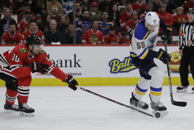 Chicago Blackhawks left wing Patrick Sharp, left, battles for the puck against St. Louis Blues defenseman Colton Parayko during the second period of an NHL hockey game Sunday, March 18, 2018, in Chicago. (AP Photo/Nam Y. Huh)