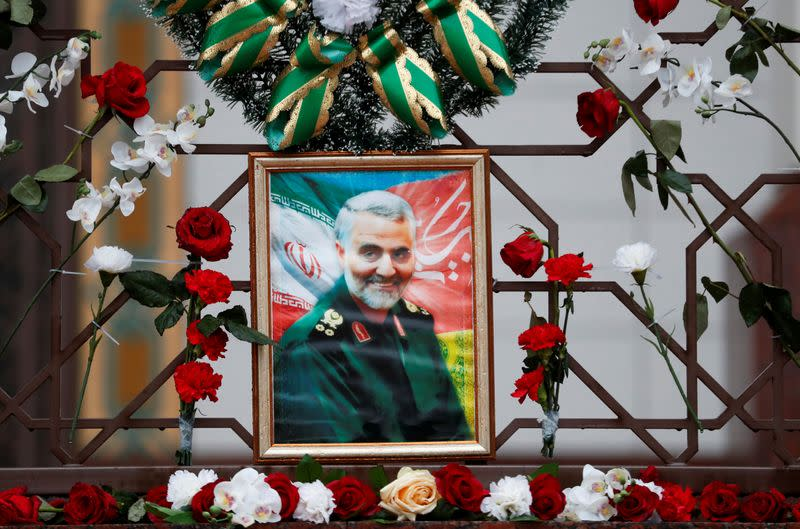 FILE PHOTO: Flowers lie around portrait of Iranian Major-General Soleimani, who was killed in airstrike near Baghdad, on Iranian embassy's fence in Minsk