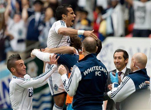 Vancouver Whitecaps' Camilo Sanvezzo, centre, of Brazil, celebrates his goal against the Portland Timbers as Russell Teibert, left, and head coach Martin Rennie, right, look on during the first half of an MLS soccer game in Vancouver, British Columbia on Saturday, May 18, 2013. (AP Photo/ The Canadian Press, Darryl Dyck)