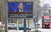 FILE - In this Jan. 7, 2021, file photo, a news screen in Essen, Germany, displays an image of Joe Biden, and a headline reading 'After chaos night in Washington, US Congress confirms Biden as next US President. For America's allies and rivals alike, the chaos unfolding during Donald Trump's final days as president is the logical result of four years of global instability brought on by the man who promised to change the way the world viewed the United States. By seeking to overturn his loss to Joe Biden, Trump upended the bedrock principle of democratic elections that the United States has sought to export around the world. (AP Photo/Martin Meissner, File)