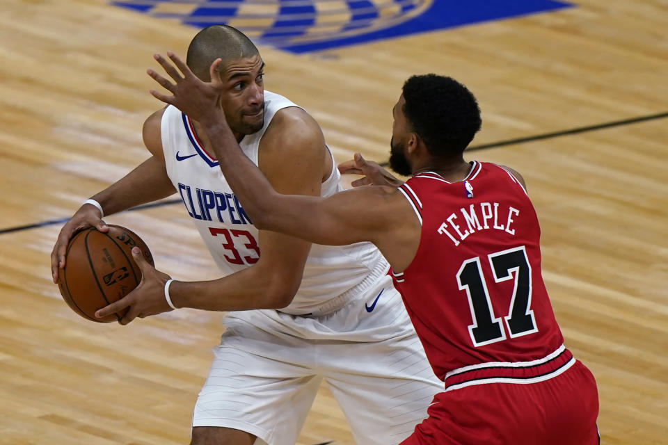 Los Angeles Clippers forward Nicolas Batum, left, looks to pass the ball as Chicago Bulls guard Garrett Temple defends during the second half of an NBA basketball game in Chicago, Friday, Feb. 12, 2021. (AP Photo/Nam Y. Huh)