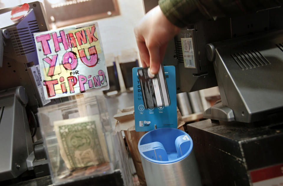 A man demonstrates the use of a DipJar, an electronic version of the tip jar found in coffee shops, on the counter of an Oren's Daily Roast in New York February 13, 2013. With a quick dip of their credit cards into the sleek machine, grateful customers are able to leave a pre-set tip (generally $1) for baristas. DipJar, a tip jar that takes plastic, located in six stores, is just one high-tech innovation seeking to make up for declining gratuities as people pay for small purchases with credit or debit cards. Picture taken February 13. To match Your Money RETAIL-SERVICE/DIPJAR                      REUTERS/Carlo Allegri  (UNITED STATES - Tags: BUSINESS SCIENCE TECHNOLOGY)