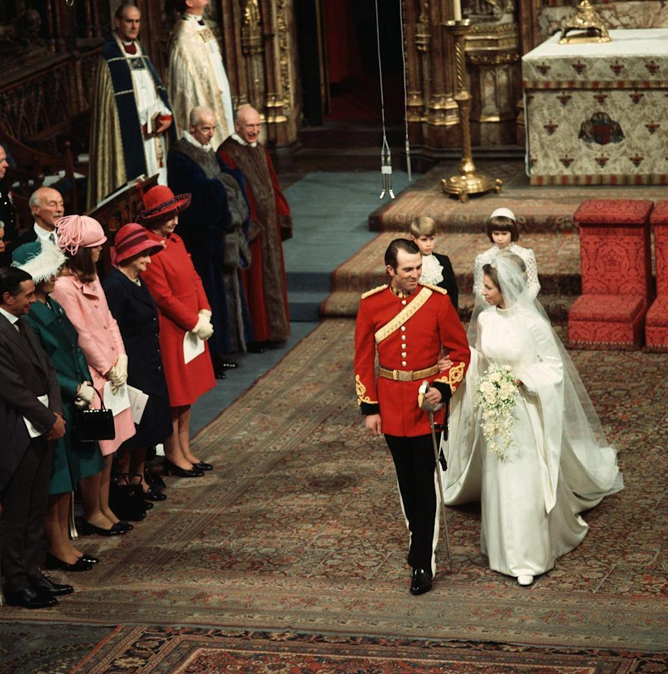 """<p><a href=""""https://www.townandcountrymag.com/society/tradition/a13075050/princess-anne-queen-elizabeth-daughter-facts/"""" rel=""""nofollow noopener"""" target=""""_blank"""" data-ylk=""""slk:Princess Anne"""" class=""""link rapid-noclick-resp"""">Princess Anne</a> and Mark Phillips share a look with one another as they process down the aisle following their nuptials in 1973. The Queen's only daughter opted for a formal ceremony at Westminster Abbey—the same church her parents were married in. <br></p>"""